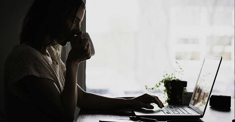 mulher tomando café na frente de um computador.