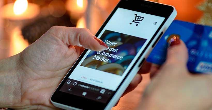 imagem de uma compra sendo realizada pelo celular com uma decoração natalina ao fundo.