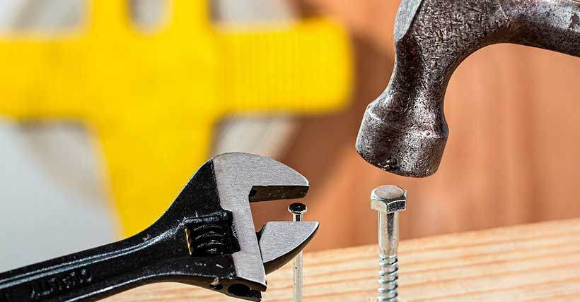 Imagem de um parafuso apertado com martelo e um preço rosqueado com uma chave.