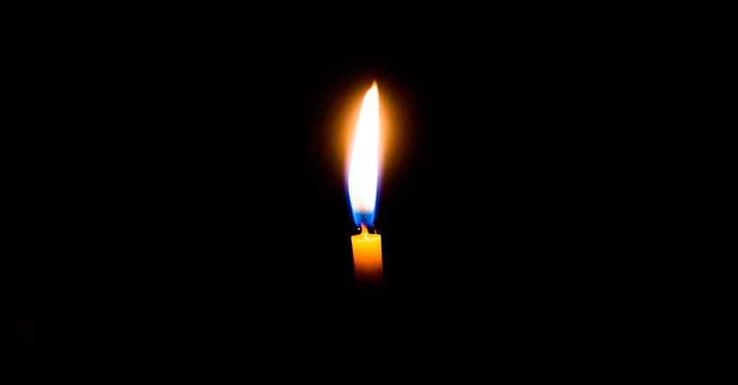 Imagem de uma vela no centro de uma tela escura.