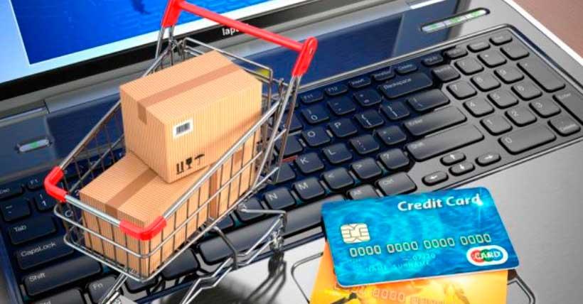 pequeno carrinho de mercado em cima de um teclado de computador com cartão de créditos do lado.