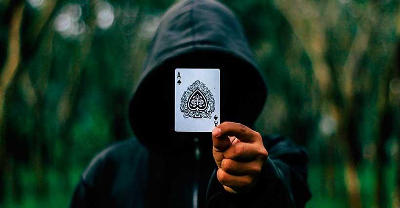 Mágico ilusionista segurando uma carta de baralho sem mostrar seu rosto.